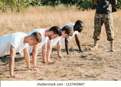 partial view of tactical instructor examining multicultural soldiers doing push ups on range