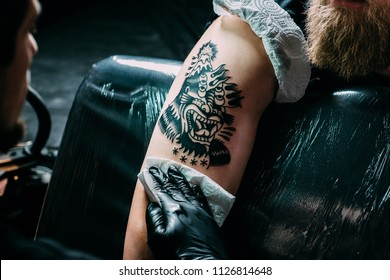 partial view of tattoo artist in gloves working on tattoo on shoulder in salon
