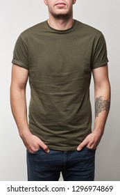 partial view of tattooed man in khaki t-shirt with copy space isolated on grey