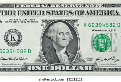 """Partial view of a USA one dollar bill showing portrait of George Washington and phrase: """"This note is legal tender for all debts, public and private""""."""