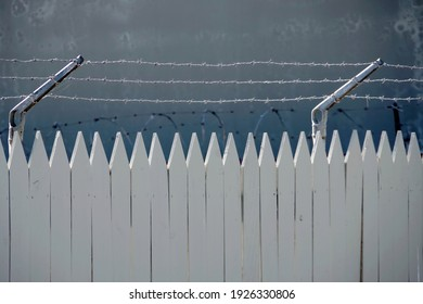 Partial view of a white wood fence with sharp tips and rows of barbed wire on top