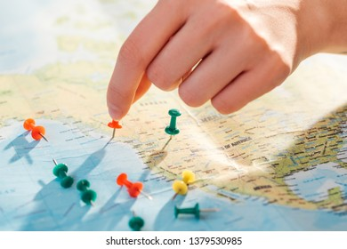 Partial view of woman and colorful push pins on world map