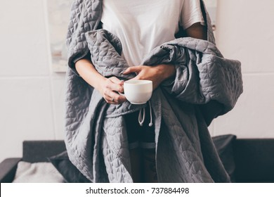partial view of woman covered in blanket holding cup of coffee at home