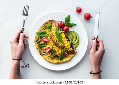 partial view of woman with cutlery in hands at tabletop with homemade omelette for breakfast