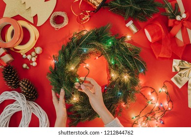 partial view of woman decorating handmade christmas wreath with lights on red background