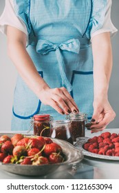 partial view of woman doing jam from strawberries and raspberries at kitchen