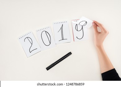 partial view of woman flipping over date written on notes symbolizing change from 2018 to 2019 isolated on white