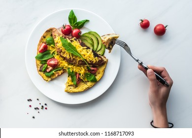 partial view of woman with fork in hand at tabletop with homemade omelette for breakfast