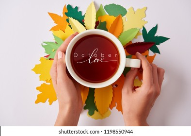 "partial view of woman holding cup of hot tea with ""october love"" inspiration on colorful papercrafted leaves"