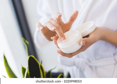 partial view of woman holding face cream in hands