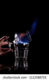 partial view of woman holding glass with burning sambuca alcohol drink on black background