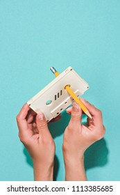 partial view of woman holding white retro audio cassette and pencil isolated on blue