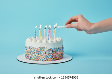 Partial view of woman lighting candles on birthday cake on blue background