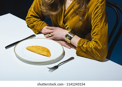 partial view of woman in luxury clothing sitting at table with meat cheburek on plate with blue backdrop
