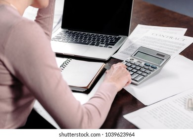 partial view of woman making calculations at table with laptop and papers at home