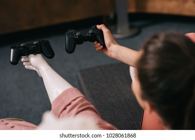 partial view of woman with manikin near by playing video game at home, loneliness concept