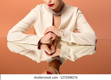 partial view of woman in pearl necklace with mirror reflection isolated on orange
