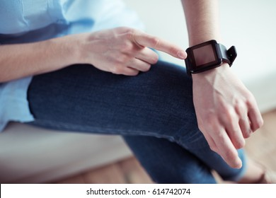 partial view of woman pointing at smartwatch screen