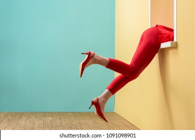 partial view of woman in red pants and shoes hanging out decorative window