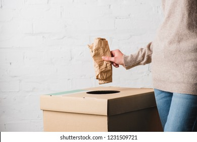 Partial view of woman throwing paper in trash bin