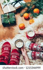 partial view of women in socks with cups of cocoa drinks at background with tangerines and wrapped christmas gifts