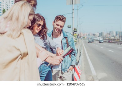 partial view of young friends looking for destination on map while traveling together