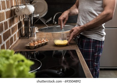 partial view of young man preparing eggs for breakfast in kitchen at home