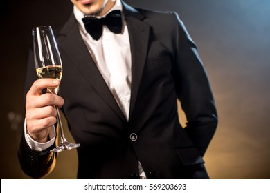 Partial view of young man in tuxedo holding champagne glass