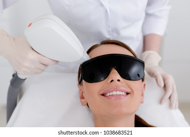 partial view of young woman receiving laser hair removal epilation on face in salon