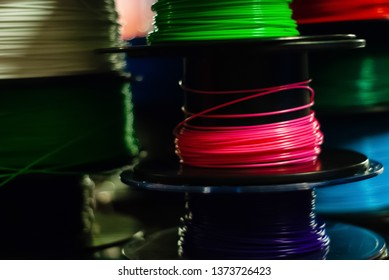 Partially blurred dark background - spools of multi-colored thermoplastic yarn for 3d pens