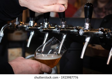 Partially blurred hand, pouring beer from silvery bar tap in a pub