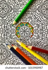 Partially completed coloring page from adult coloring book with symmetric designs with several color pencils