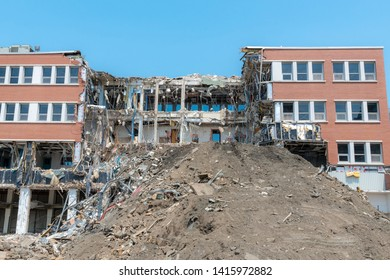 A partially demolished building. Much of the center of the building is missing, and there is a large pile of dirt in front. Lots of debris and hanging wires. Bright sunny day.