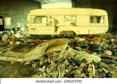 Partially destroyed camping trailer standing in the middle of horrible dump inside abandoned factory.
