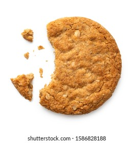 Partially eaten crunchy oat and wholemeal biscuit with crumbs isolated on white. Top view.