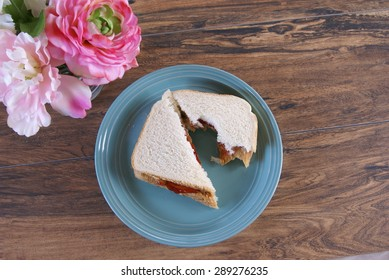 Partially eaten peanut butter and jelly white bread sandwich laying on a green plate.