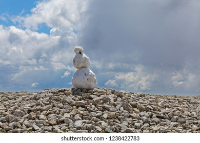 Partially melted sad snowman against moody sky