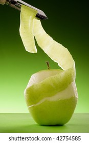 partially peeled green apple on green board isolated on graduated green background