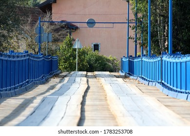 Partially renovated wavey old wooden bridge with new blue metal frame on each side and strong support surrounded with large dense trees and family houses in background