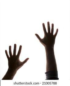 partially silhouetted hands backlit and on white reaching up as if trapped
