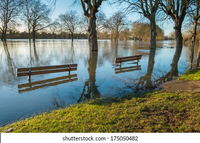 Partially submerged benches on a flooded riverbank in Windsor