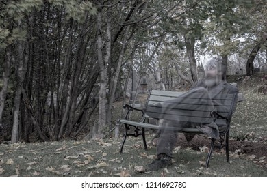 A partially transparent ghost of a man sitting on a bench in a grave yard at dusk. Trees and tombstones in the background. Low saturation.