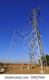 A partially-built replacement tower stands next to the old high voltage transmission tower