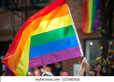 Participant with large backlit rainbow flag in the annual Gay Pride Parade as it passes through Greenwich Village.