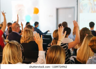 Participants of the conference vote and signal the speaker with their hands up in a special audience with a projector and screen. Education and training of employees. Soft focus and beautiful bokeh.