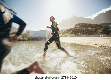 Participants running into the water for start of a triathlon. Two triathletes rushing into water.