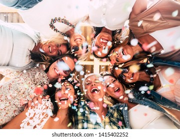 Particular point of view of nine women in group celebrating the friendship. Nine caucasian people enjoying the party with colored confetti. Happy lifestyle. Sunset on terrace