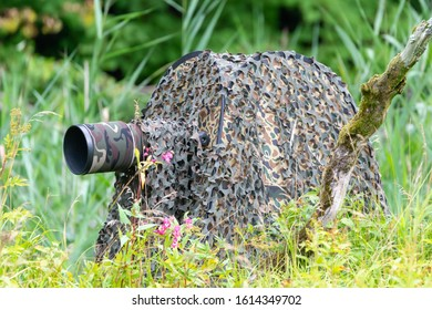 Partille, Sweden, August 29, 2018. Photographer hides in a camouflage colored photography hide, waiting with his camera gear to take photos of birds and animals.