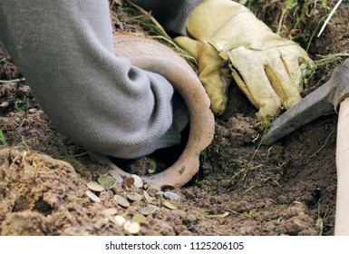 Partly buried old clay jar with money in the land, woman is trying pick up