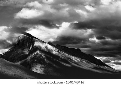 A partly cloudy sky creates interesting light play on the broad slopes of Mt. Rundle. Banff, Alberta, Canada